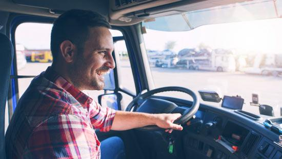 Man smiling and driving a truck