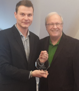 Tobias Packheiser, left, receives the Descartes Excellence and Innovation Award from Robert Beauchemin, EVP of Sales at Descartes.